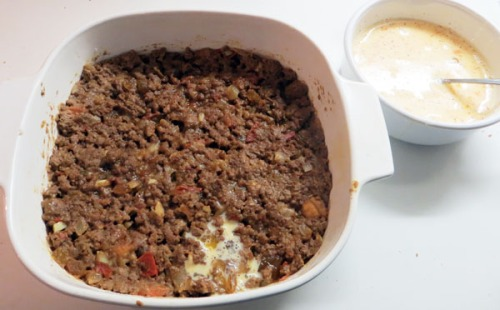 Pack ground beef in dish for bobotie